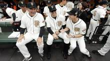 From left, San Francisco Giants manager Bruce Bochy sits with Barry Zito and Tim Lincecum during a ceremony in which the team received its 2012 World Series rings. (Ezra Shaw/The Associated Press)