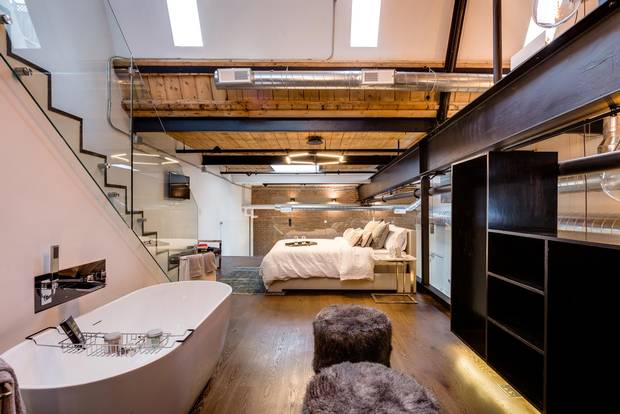 The 'mezzanine' floor of the unit features an open-air master bedroom and an exposed bathtub, along with a vanity unit and a wet room that has a shower and toilet.