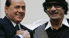 Libyan leader Moammar Gadhafi, right, clasps hands with Italian Premier Silvio Berlusconi in Rome in this 2009 photo. (Gregorio Borgia/Gregorio Borgia/Associated Press)