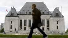 A woman walks past the Supreme Court of Canada in Ottawa. (Tom Hanson/The Canadian Press)
