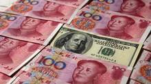 A U.S. $100 banknote is placed next to 100 yuan banknotes in this picture illustration taken in Beijing in this October 16, 2010 file photo. China took a milestone step in turning the yuan into a global currency on April 14, 2012, by doubling the size of its trading band against the dollar, pushing through a crucial reform that further liberalizes its nascent financial markets. (PETAR KUJUNDZIC/REUTERS/PETAR KUJUNDZIC/REUTERS)