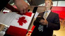 Chris Alexander, Canada'ss Minister of Citizenship and Immigration, welcomes 60 new citizens at a special citizenship ceremony at the Canadian National Exhibition in Toronto on Aug. 22, 2013. (PETER POWER/THE GLOBE AND MAIL)