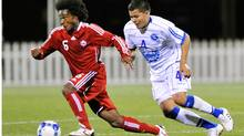 Julian de Guzman #6 of Canada keeps control of the ball in front of Jose Henriquez #4 of El Salvador at Crew Stadium on July 7, 2009 in Columbus, Ohio. (Jamie Sabau/2009 Getty Images)