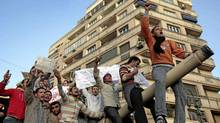 Egyptian anti-government protesters chant slogans as they stand atop an Egyptian army tank during a protest in Tahrir square in Cairo, Egypt, Saturday, Jan. 29, 2011. (Lefteris Pitarakis/Lefteris Pitarakis/The Associated Press)