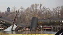 Derailed freight train cars sit semi-submerged in the waters of Mantua Creek in Paulsboro, New Jersey, November 30, 2012. A rail bridge collapsed on Friday over a creek in southern New Jersey, causing a Conrail freight train to derail and spill hazardous chemicals into the water, authorities said. (ANDREW BURTON/Reuters)
