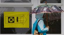 FILE PHOTO: A woman carries an umbrella as she enters a polling station to vote in the federal election in Sidney, B.C., on Vancouver Island, on Monday May 2, 2011. (DARRYL DYCK/The Canadian Press)