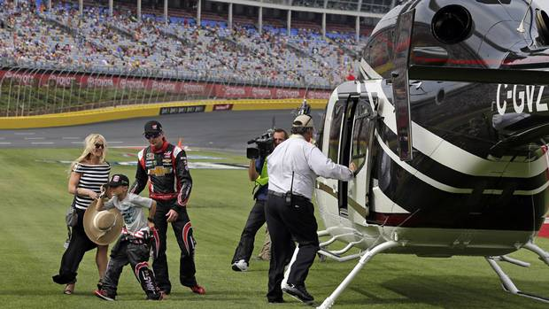 Driver Kurt Busch, right, arrives with girlfriend Patricia Driscoll, left, and her son, Houston, centre, for the NASCAR Sprint Cup series Coca-Cola 600 auto race at Charlotte Motor Speedway in Concord, N.C., Sunday, May 25, 2014. Busch finished sixth in the Indianapolis 500 race earlier.
