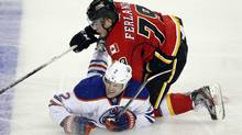 Edmonton Oilers' Jeff Petry, left, grimaces as Calgary Flames' Michael Ferland crashes down on him during third period NHL pre-season hockey action in Calgary, Alta., Saturday, Sept. 14, 2013. The Edmonton Oilers beat the Calgary Flames 3-2. (JEFF MCINTOSH/THE CANADIAN PRESS)