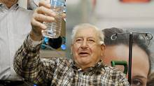 Henry Morello, 84, of Anthem, Ariz., toasts with a bottle of water as he talks about surviving his five-day ordeal in the desert during a news conference at John C. Lincoln Hospital in Phoenix. (Ross D. Franklin/AP)