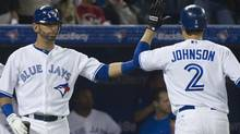 Toronto Blue Jays right fielder Jose Bautista, left, celebrates with Blue Jays shortstop Kelly Johnson, right, after Johnson hit a three run homerun against the Texas Rangers during third inning AL action in Toronto on Tuesday. (Nathan Denette)