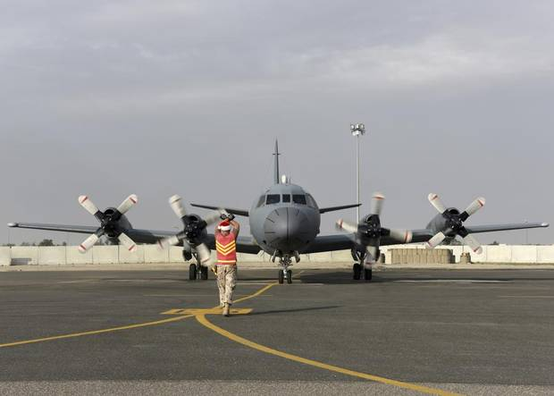 An aircraft technician from Air Task Force – Iraq marshals a CP-140 Aurora aircraft into Camp Canada in Kuwait on December 12, 2015 during Operation IMPACT.