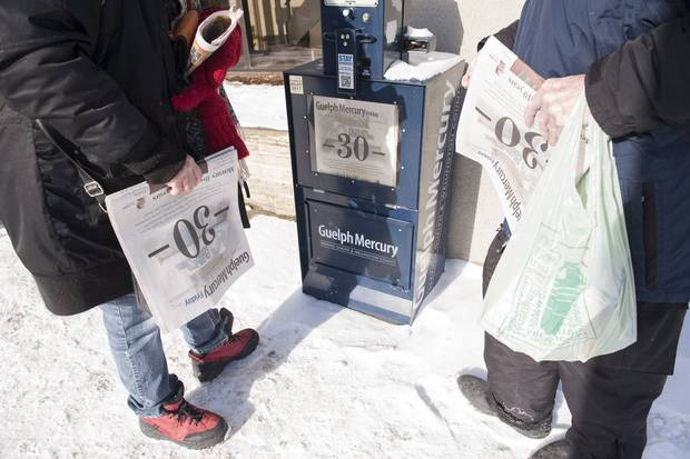 Jan. 29, 2016: Nina Menard, left, and Lex Stephenson buy copies of the final edition, its cover inscribed with a large '-30-', a traditional newspaper reporter's mark to denote the end of a story.
