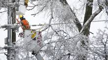 Workers repair power lines on Bayview Ave. in Toronto, Ontario, Monday December 23, 2013 following the weekend ice storm which knocked out power to thousands of homes. (Kevin Van Paassen/The Globe and Mail)
