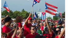 People wave flags of Cuba (blue stripes) and Puerto Rico (red stripes) during the celebrations for the 58th anniversary of the Moncada barrack attack, at Revolution Square in Ciego de Avila, in the Cuban province of the same name, on July 26, 2011. (ADALBERTO ROQUE/AFP/Getty Images/ADALBERTO ROQUE/AFP/Getty Images)