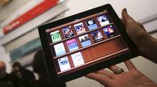 A woman holds up an iPad with the iTunes U app after a news conference introducing a digital textbook service in New York in this January 19, 2012, file photo. (SHANNON STAPLETON/SHANNON STAPLETON/REUTERS)