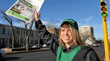 Promoter Brittany Bartel holds up a copy of a Metro newspaper in downtown Regina. The commuter daily will begin free daily distribution in Regina and Saskatoon on Monday. (Roy Antal/The Canadian Press/Roy Antal/The Canadian Press)