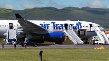 A Canadian Air Transat plane with its emergency slides deployed, sits on the tarmac of Lages airport in the Azores Terceira island, after an emergency landing, Friday, Aug, 24, 2001, in the north Atlantic Portuguese archipelago. (HUMBERTA AUGUSTO/AP)