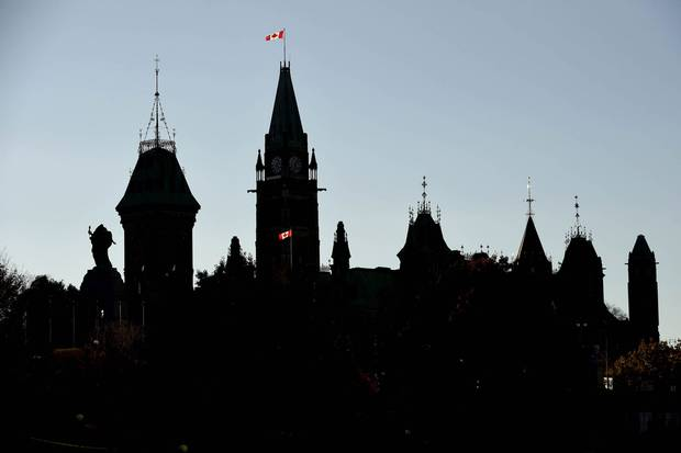 A Canadian flag flies outside Parliament Hill, backlit by the setting sun, on Oct. 22, 2014, after much of the city's downtown was in lockdown because of a shooting in Centre Block and at the National War Memorial.