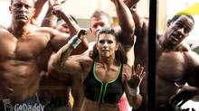 In this image released by GoDaddy.com on Wednesday, Jan. 22, 2014, NASCAR driver Danica Patrick, center, wearing a muscle suit, appears with bodybuilders in an upcoming Super Bowl commercial shot on location in Long Beach, Calif. (AP)