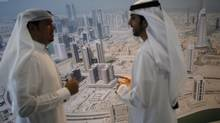 Businessmen chat during the Cityscape real estate exhibition in Dubai Oct. 2, 2012. Dubai's real-estate market blew up spectacularly in 2008. (AHMED JADALLAH/REUTERS)