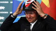 Eric Lamaze puts on his Team Canada helmet after he was named to the Canadian Olympic equestrian team in Calgary, Alberta, July 5, 2012. Lamaze won the gold medal at the 2008 summer Olympics and will represent Canada at this year's summer Olympics in London. (TODD KOROL/REUTERS)