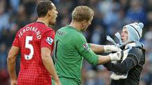 Manchester City's Joe Hart (C) prevents a supporter from reaching Manchester United's Rio Ferdinand (L)  after being struck by an object thrown from the crowd during their English Premier League soccer match against Manchester City at The Etihad Stadium in Manchester, northern England December 9, 2012. (Reuters)