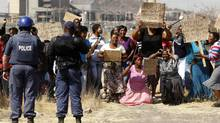 Policemen look on as women carrying placards chant slogans in protest against the killing of miners by South African police on Thursday, outside a South African mine in Rustenburg, 100 km northwest of Johannesburg, August 17, 2012. (SIPHIWE SIBEKO/REUTERS)