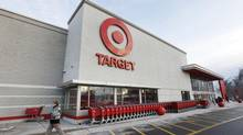 In this Dec. 19, 2013, file photo, a passer-by walks near an entrance to a Target retail store in Watertown, Mass. (Steven Senne/AP)