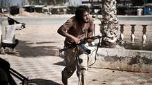 Libyan rebels come under fire from Gadhafi loyalists in Bir Ghanam, southwest of Tripoli. (Colin Summers/AFP/Getty Images)