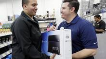 May all your PlayStation shopping experience be as satisfying and awkward looking as this one: Andy Varadez, left, from Chicago, purchases a Sony PlayStation 4 from Best Buy sales manager Michael Centeno at Lincoln Park Best Buy store in on Friday, Nov. 15, 2013. (Nam Y. Huh/AP)