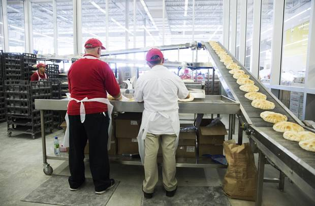 Workers pack freshly baked pitas into plastic sleeves at Adonis.