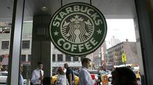 People walk past the Starbucks outlet on 47th and 8th Avenue in New York. (LILY BOWERS/LILY BOWERS/REUTERS)