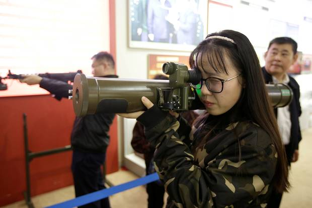 A visitor handles a model of a weapon at a military simulator area.