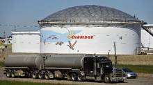 A storage tank looms over a highway at the Enbridge Edmonton terminal. (Dan Riedlhuber/Reuters)