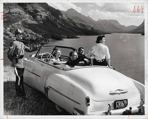 Gar Lunney, [Corporal W.W. MacLeod of the Royal Canadian Mounted Police gives directions to tourists in Waterton Lakes National Park, Alberta], ca. 1958, gelatin silver print.