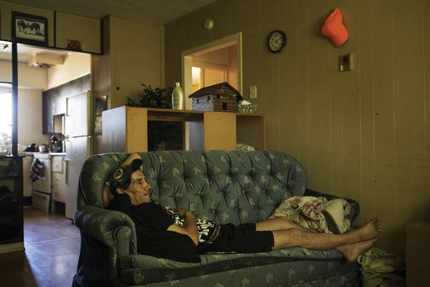 Marleah's father, James Trout, watches television inside their two-bedroom home. Mr. Trout sleeps on the couch so Marleah and her brother can have their own rooms.