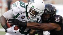 Saskatchewan Roughriders' Will Ford (30) tries to break away from the clutches of Ottawa Redblacks' TJ Hill (21) during CFL football action in Ottawa, Saturday August 2, 2014. (Fred Chartrand/The Canadian Press)