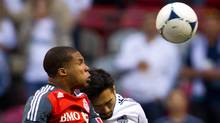 Toronto FC's Ryan Johnson, left, and Vancouver Whitecaps' Jun Marques Davidson, of Japan, battle for the ball during the first half of a Canadian Championship soccer game in Vancouver, B.C., on Wednesday May 16, 2012. (Darryl Dyck/CP/Darryl Dyck/CP)