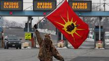 A protester waves a flag in Sarnia as Idle No More members blocked traffic at the Blue Water Bridge to the United States for an hour Saturday. (Dave Chidley/THE CANADIAN PRESS)