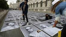 The artist known as JR pastes photos on the sidewalk as part of a public-access art installation at Somerset House in London. (SUZANNE PLUNKETT/REUTERS)