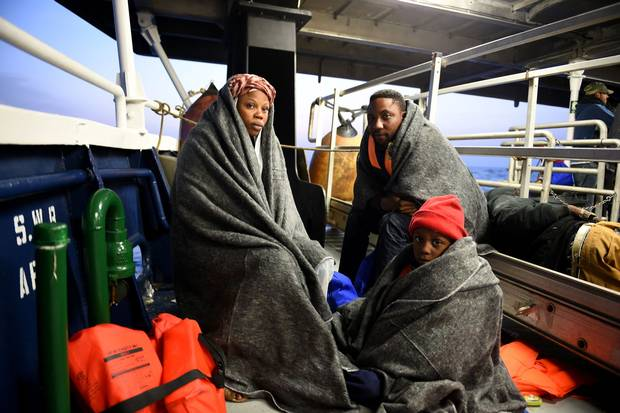 A family from Nigeria rests with dry blankets on the deck of the boat MY Phoenix, just minutes after they were rescued .