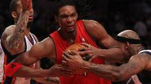 Chris Bosh #4 of the Toronto Raptors drives to the basket between Wilson Chandler #21 and Al Harrington #1 of the New York Knicks at Madison Square Garden on January 28, 2010 in New York, New York. NOTE TO USER: User expressly acknowledges and agrees that, by downloading and or using this photograph, User is consenting to the terms and conditions of the Getty Images License Agreement. (Photo by Nick Laham/Getty Images) (Nick Laham/2010 Getty Images)