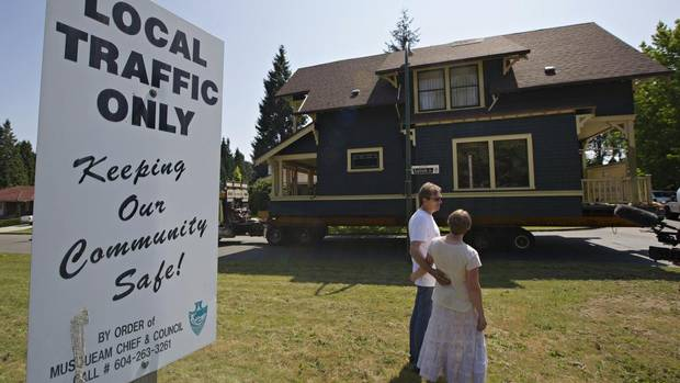 Ben Ford and his wife Jen watch as their house is moved along a street in Vancouver on July 26. The house was lifted off its foundations so it could be moved, by truck and sea barge, to Vancouver Island. (ANDY CLARK/REUTERS)
