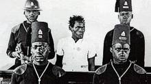"A Kenyan ""Mau Mau"" freedom fighter Waruhiu Itote (C), also known as General China, stands in the dock in a British colonial court during the 1950's Mau Mau independence rebellion, in this undated file picture issued by the Kenya National Archives. A British historian David Anderson said Britain should apologize for atrocities it committed during the conflict but he added that a reparations campaign by the former fighters may deepen the rifts their revolt opened among Kenyans. REUTERS/Kenya National Archives - Ho (HO/REUTERS)"