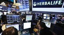 Traders work at the post that trades Herbalife stock on the floor of the New York Stock Exchange in this file photo. (BRENDAN MCDERMID/REUTERS)