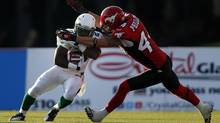 Saskatchewan Roughriders' Jock Sanders, gets tackled Calgary Stampeders' Justin Phillips, during first quarter CFL football action in Calgary, Alta., Friday, Aug. 9, 2013. (Jeff McIntosh/THE CANADIAN PRESS)
