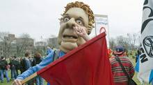 A studen wears a mask depicting Quebec Premier Jean Charest during a protest against tuition hikes in Montreal on April 14, 2012. (Graham Hughes/Graham Hughes/The Canadian Press)