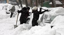 Motorists dig out their cars in Montreal on Dec. 15, 2013, as more than 20 cm of snow fell. (RYAN REMIORZ/THE CANADIAN PRESS)