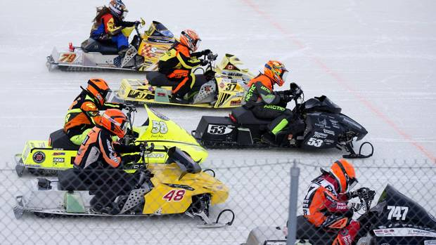 Snowmobiles race at a track in Valcourt, Quebec on Feb. 10, 2017.