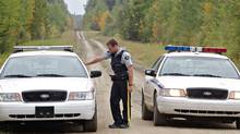 RCMP officers block the road near the entrance to a property of interest as police continue the investigation into missing St. Albert couple Lyle and Marie McCann in this September 2010 file photo. (Jason Franson for the Globe and Mail)